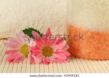 Bath salt, towel and two pink flowers