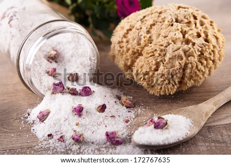 Bath salt with rose flavour, spoon and a sponge - stock photo