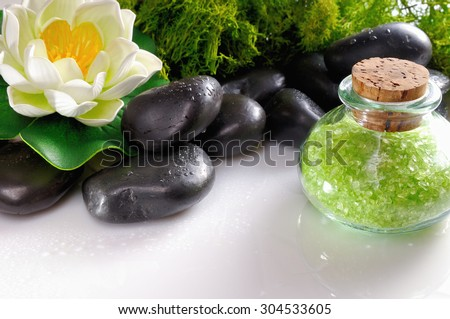 Bath salts close up with black stones and moss flower glass on white table. Horizontal composition