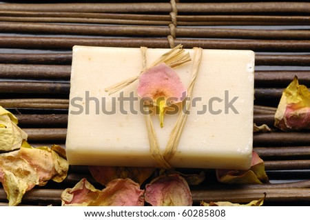 Bath spa- natural soap with rose petals on mat - stock photo