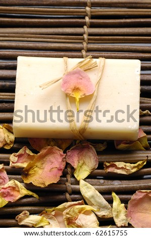 Bath spa- natural soap with withered rose petals on mat - stock photo