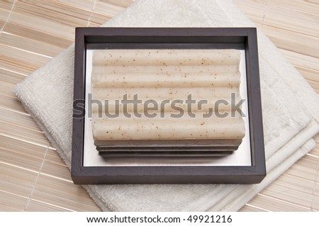 Bath spa scene with soap and towel on a bamboo mat. - stock photo