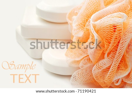 Bath sponge with natural vegetable oil soaps on cream colored background with copy space.  Macro with shallow dof. - stock photo
