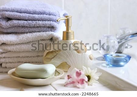 Bath still life ( soap bar, soap pump, flowers, towels) - stock photo