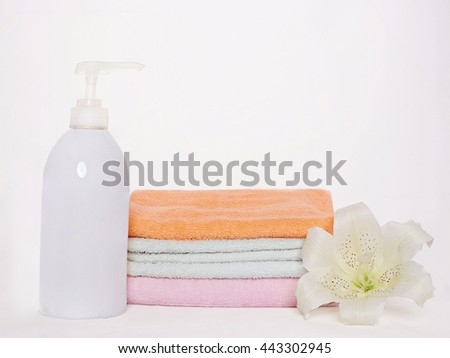 Bath still life.towels, flower and lotion bottle - stock photo