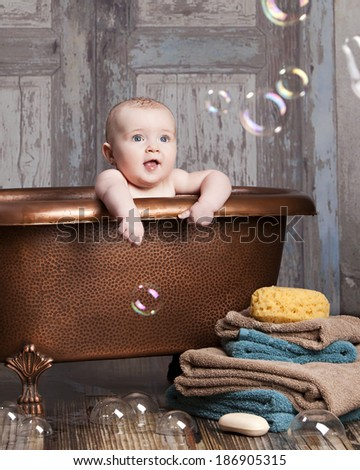 Bath time fun!  Adorable baby girl in a claw tooth bathtub looking at bubbles.
