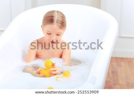 Bath time is fun. Closeup image of a cute little girl taking a bath and playing with rubber ducks while sitting in a luxurious bathtub  - stock photo