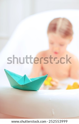 Bath time is fun. Selective focus image of a cute little girl taking a bath and playing with rubber ducks and paper ships while sitting in a luxurious bathtub  - stock photo