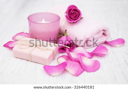 Bath towels, candle and soap with pink roses on a old wooden background
