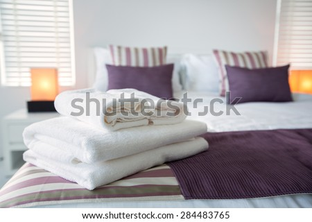Bath towels on the bed of hotel bedroom - stock photo