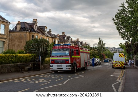 BATH, UK - JULY 10: Fire-fighters attend a fire at a Victorian residential house in Bath. The fire crew attended even though there was a public sector strike. July, 2014 at Combe Park, Bath, Somerset. - stock photo