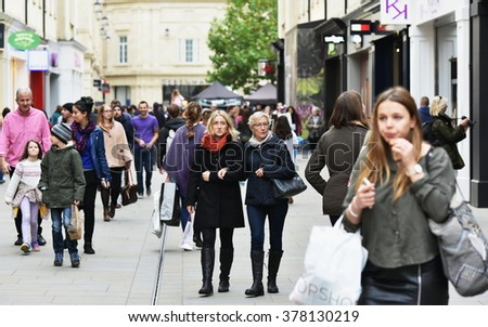 BATH, UK - OCT 18, 2015: Crowds of people walk along a busy shopping street. Picturesque Bath is a UNESCO World Heritage city and popular travel destination with over 4 million visitors each year.