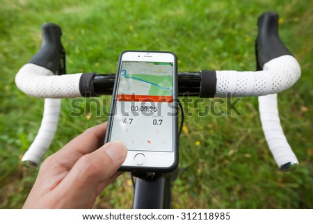 BATH, UK - SEPTEMBER 1, 2015 : Close-up of a smartphone mounted onto the handle bars of a road bike in a park. The phone is displaying the Strava app, which shows navigation and pace information. - stock photo