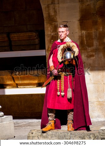 BATH, UNITED KINGDOM - APRIL 11, 2015: Actor in Roman soldier costume at history site Roman Bath. The Baths are a major tourist attraction receiving more than one million visitors a year. - stock photo