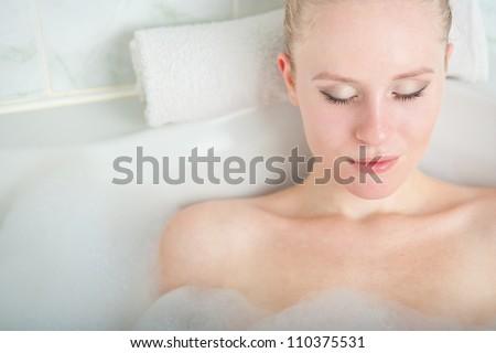 Bath woman enjoying bathub. Naturally beautiful female relaxing in bath with foam in bathroom - stock photo