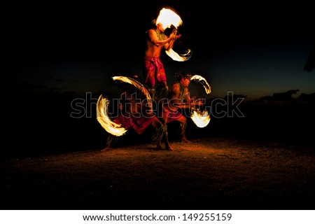 Bathed in an orange glow, three male fire dancers on a Hawaiian beach, create a human pyramid and spin sticks with fire on either side. The glow of the fire illuminates the ground.