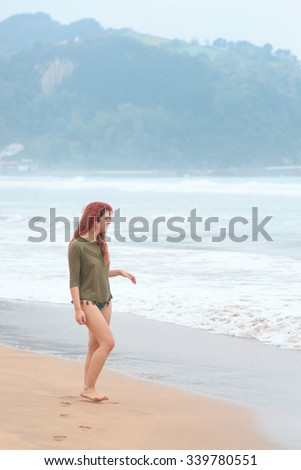 bather girl on the beach on a stormy day in winter