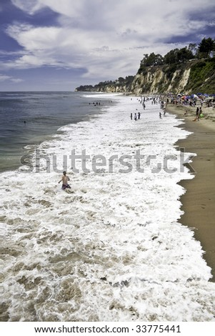 Bathers enjoy the surf at Paradise Cove in Malibu, California
