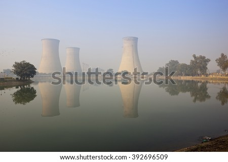 Bathinda, Punjab, India. February 9th 2016. cooling towers and chimneys of Guru Nanak Dev thermal power plant viewed across the lake on a misty morning.