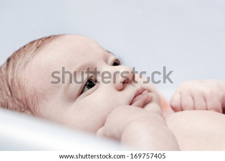 Bathing a young 3 month baby. Close up face portrait