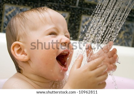 bathing and smiling baby under the douche - stock photo