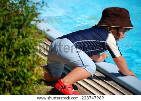 Bathing fun A little child is playing with a watering can.  - stock photo