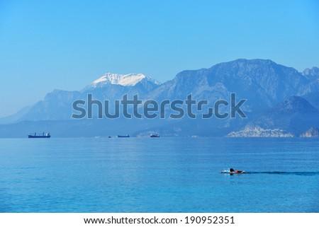 Bathing in the Mediterranean sea against snowy mountains near Antalya, Turkey - stock photo
