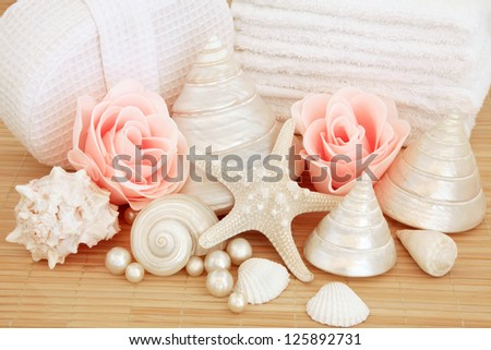 bathroom accessories of rose soap petal buds sea shells pearls with white towel stack