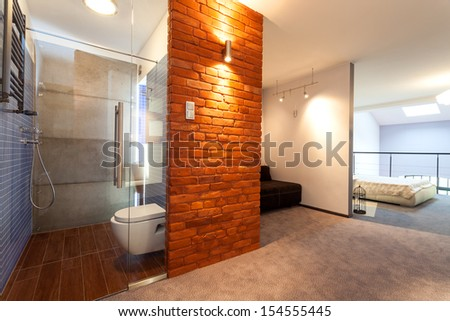 Bathroom and bedroom in a modern loft with an entresol and brick wall - stock photo