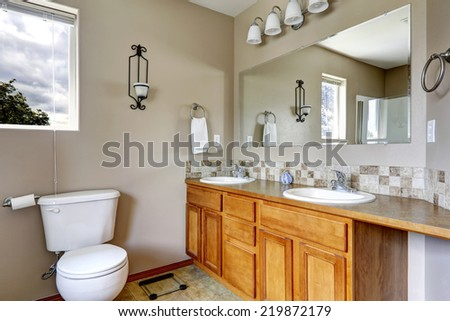 Bathroom cabinet with two sinks and tile trim. Large mirror.