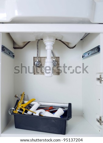 Bathroom cabinet with washbasin plumbing fixtures and plumber's toolbox - stock photo