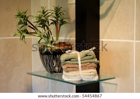 Bathroom decor with pot plant and towels - stock photo