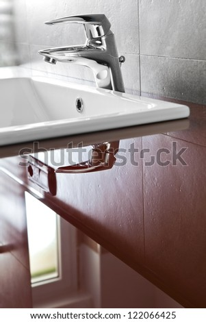 Bathroom faucet closeup with riflection on the red translucent board - stock photo