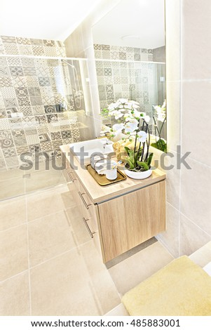 Bathroom high angle view, focusing the counter top with white flowering plant and green leaves with a sink and tap beside towels, the mirror on the wall is giving the reflection of the shower area