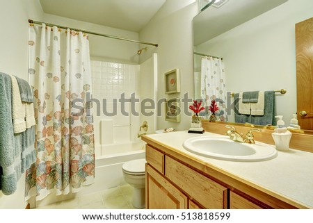 Bathroom interior in marine style. Shower curtain with sea shells pattern, tile floor. Northwest, USA