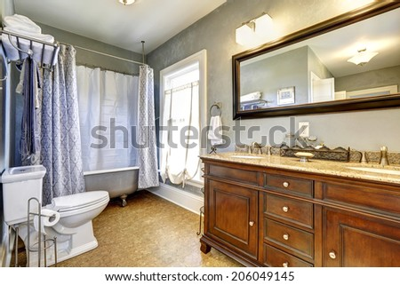 Bathroom interior in old house with old bathroom vanity cabinet and claw foot tub