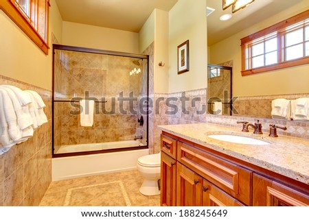 Bathroom interior. Mocha tile wall trim, brown vanity with mirror and bath tub with glass door - stock photo