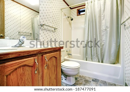 Bathroom interior. View of wooden vanity with mirror, toilet and bath tub with curtains