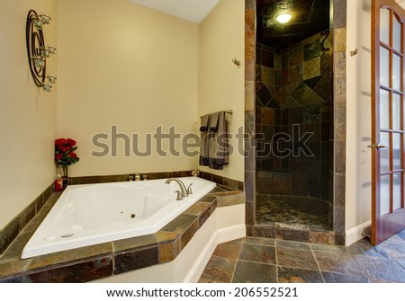 Bathroom interior with dark tile floor and tile shower trim. View of white whirlpool tub decorated with red roses
