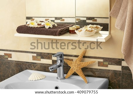 Bathroom interior with sink, shelf, towel, starfish and salt - stock photo