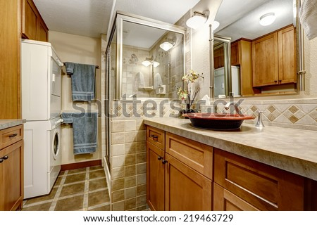 Bathroom interior with tile trim, glass screened shower and laundry area