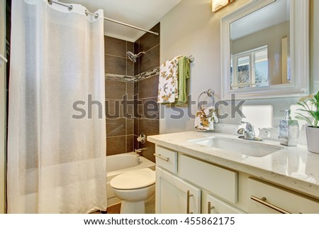 Bathroom interior with white cabinets, tile floor and bath tub