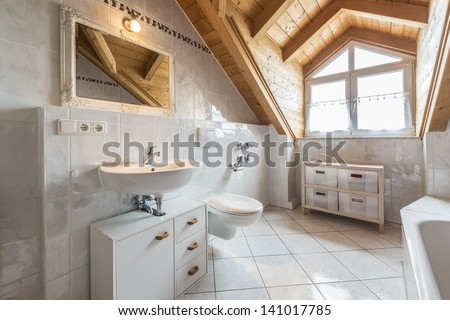 bathroom of a flat in attic with basin, mirror, light, window, toilet, bathtub, cabinets and wooden ceiling - stock photo