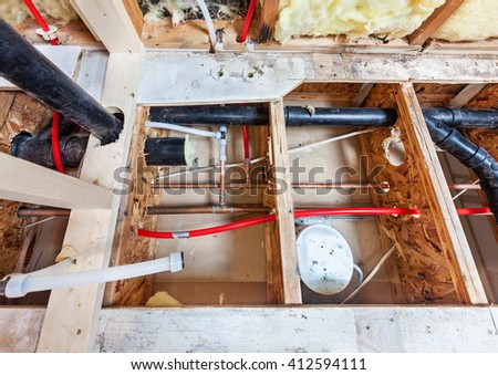 Bathroom remodel showing under floor plumbing work connecting old copper pipes to new plastic ones and moving vent pipes - stock photo