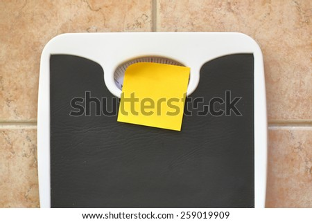 Bathroom scale with blank memo sticker. Diet and fitness concept - stock photo