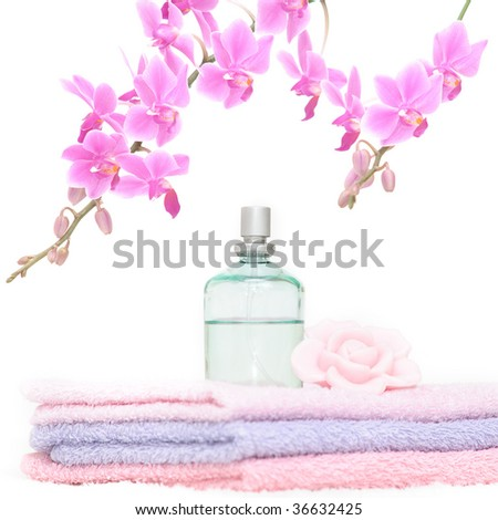 Bathroom set with three towels, a perfume bottle, one rose petal shaped piece of soap and a decorative pink orchid - stock photo