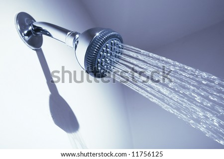 Bathroom shower head on blue background - stock photo