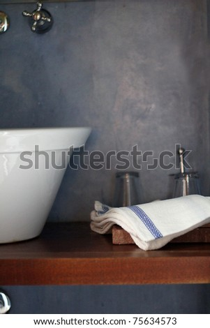bathroom sink and towel against a blue wall