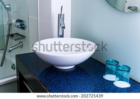 Bathroom sink counter tap mixer glass blue - stock photo