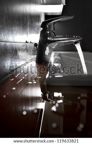 Bathroom sink silhouette lighted by backlight - stock photo